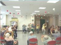 高齢者の方が大勢輪になり、体操をしている風景の写真
